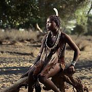 Boree sits for a portrait on an old tree branch on a dry river bed, Lower Omo Valley, Ethiopia.