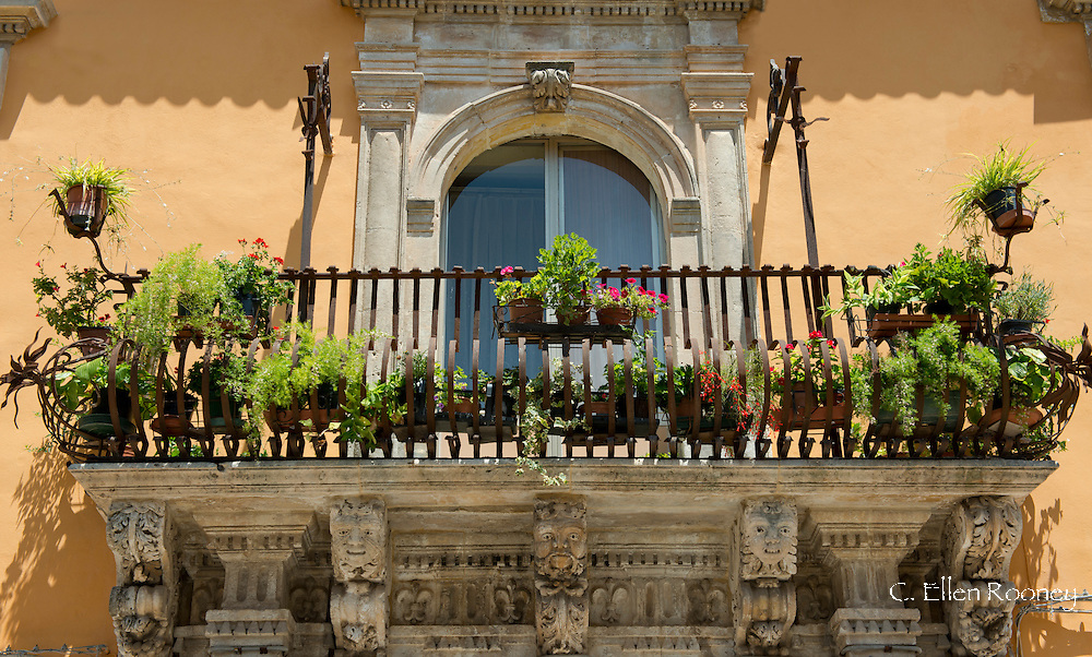 A flower filled balcony with Baroque stone carvings in Syracuse, Sicily, Italy