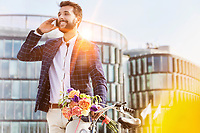 Portrait of young attractive businessman holding boquet of flowers while talking on smartphone