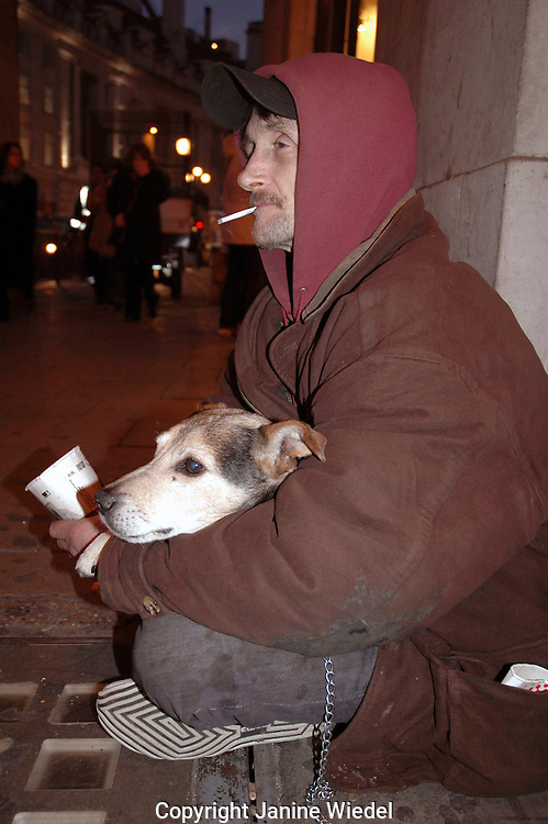 Homeless man begging with his dog on streets of London.