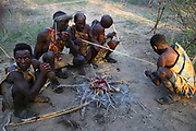 Hadzabe tribesmen sitting around a campfire cooking meat  Photographed at Lake Eyasi, Tanzania
