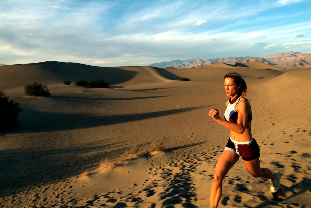 Woman running sand dunes in Death Valley, CA.