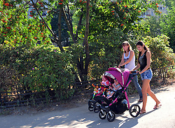 New mothers wheel their children through a sunny Saturday afternoon near the apartments directly opposite the Salt Pier, where river boats moor in St. Petersburg, Russia.