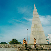Two girls in bikinis sunbathing in front of a monument in Brazil, 1990's