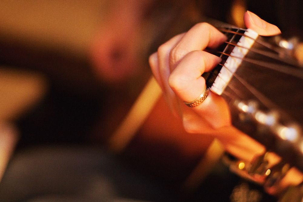 Shallow depth of field image of a guitar being played. We can see guitar strings, the guitar stem and a hand wearing a ring on one finger.