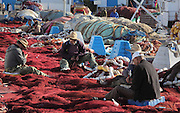 Men mending red fishing nets at the fishing harbour at M'diq or Rincon, M'diq-Fnideq, on the Mediterranean coast of Morocco. M'diq has 2 harbours, one for tourism and the other for its traditional industry of fishing. Picture by Manuel Cohen