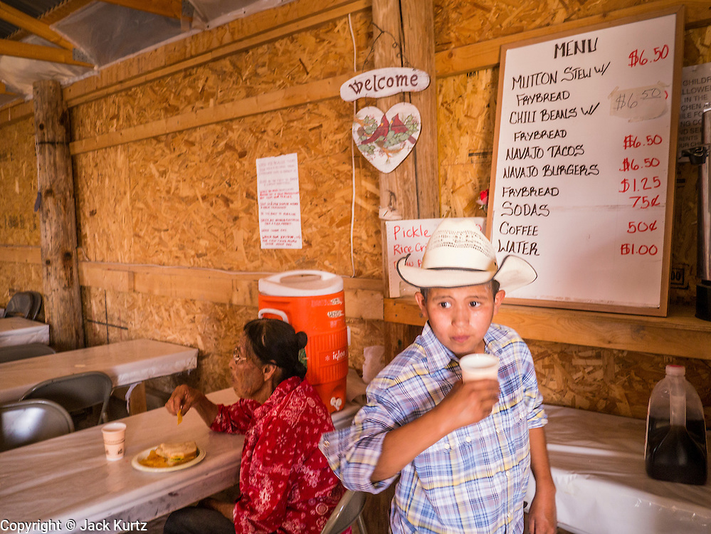 "13 JULY 2012 - FT DEFIANCE, AZ: A boy drinks an iced tea in the chow hall at the 23rd annual Navajo Nation Camp Meeting in Ft. Defiance, north of Window Rock, AZ, on the Navajo reservation. Preachers from across the Navajo Nation, and the western US, come to Navajo Nation Camp Meeting to preach an evangelical form of Christianity. Evangelical Christians make up a growing part of the reservation - there are now more than a hundred camp meetings and tent revivals on the reservation every year. The camp meeting in Ft. Defiance draws nearly 200 people each night of its six day run. Many of the attendees convert to evangelical Christianity from traditional Navajo beliefs, Catholicism or Mormonism. ""Camp meetings"" are a form of Protestant Christian religious services originating in Britain and once common in rural parts of the United States. People would travel a great distance to a particular site to camp out, listen to itinerant preachers, and pray. This suited the rural life, before cars and highways were common, because rural areas often lacked traditional churches. PHOTO BY JACK KURTZ"