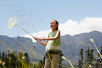 Girl (7-9) standing in field holding butterfly net low angle view.
