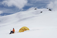 Hiker using laptop outside of tent on snowy mountain peak