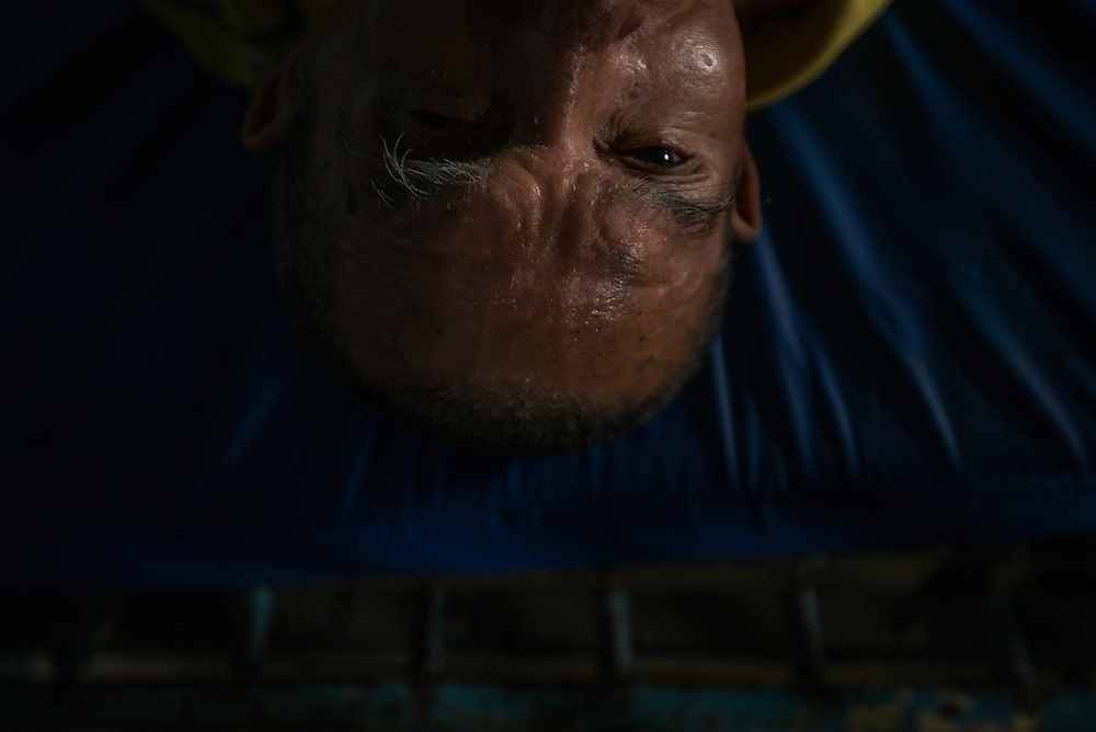 BARQUISIMETO, VENEZUELA - JULY 28, 2016: José Herrera rests in his shared hospital room. Herrera is diagnosed with senile dementia, and was abandoned by his family, living in the streets before a nonprofit organization found him and brought him to El Pampero.  The economic crisis that has left Venezuela with little hard currency has also severely affected its public health system, crippling hospitals like El Pampero Psychiatric Hospital by leaving it without the resources it needs to take care of patients living there, the majority of whom have been abandoned by their families and rely completely on the state to meet their basic needs. The hospital has not employed a psychiatrist for over two years. Drugs used to combat bipolar disorder, epilepsy, schizoaffective disorder and chronic anxiety are now in short supply, as are numerous sedatives and tranquilizers needed to care for patients. Members of the nursing staff debate daily which patients are the most unstable, to decide which patients will receive pills and which will go without. When a patient loses control, often the only thing they can do is restrain them, or lock them in an isolation cell to prevent them from hurting themselves, other patients and members of the staff.  PHOTO: Meridith Kohut