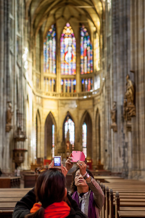 Tourists are photographing St. Vitus Cathedral with their mobile phones.