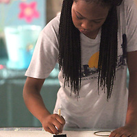 Ca Leya Patterson, 12, of Tupelo, paints her patteren onto her bulletin board art project at SHINE Camp at HealthWorks in Tupelo. SHINE Camp is week long camp put on by the Junior Auxiliary of Tupelo for upcoming middle school girls that promotes positive self-esteem through devotions, drama, art, physical excerise and group discussions.