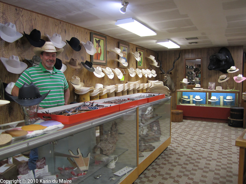 Cowboy hat maker in his store in New Braunfels, Texas. Straw and felt hats. African buffalo and kudu on the wall!