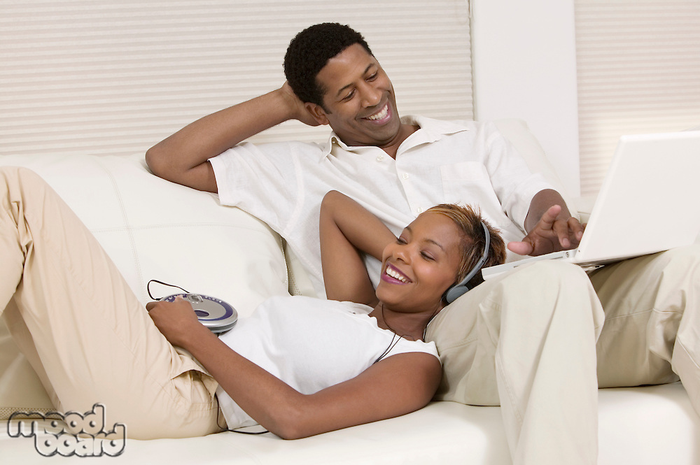 Couple Relaxing on Couch with Headphones and Laptop