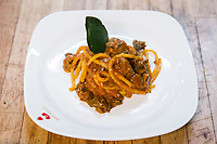 NAPLES, ITALY - 4 JANUARY 2019: Bucatini with sautéed meat are seen here at Janarius, a restaurant in Naples, Italy, on January 4th 2019.<br /> <br /> Janarius is a typical Neapolitan gourmet restaurant and shop founded by Francesco Andoli in September 2018 in via Duomo, in front of the Naples's Duomo and treasure of Saint Janarius.