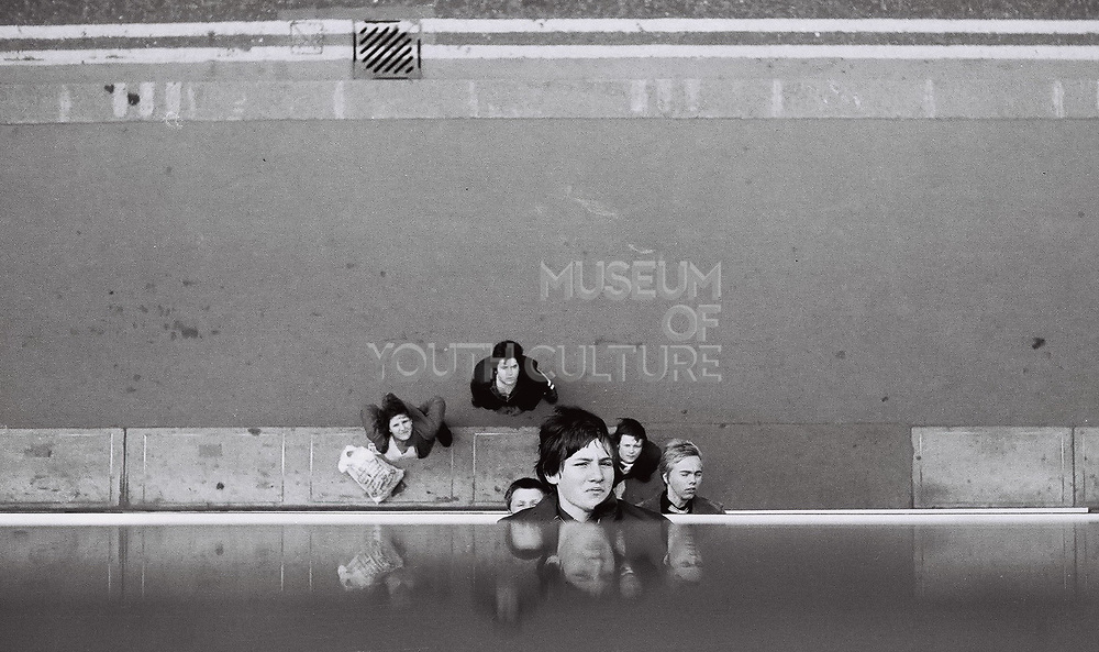 Six teenage friends sticking heads out of, and standing at the bottom of wall. London, UK, 1980s.