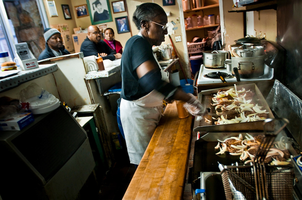 """Miss Ann frying burgers...Ann's Snack Bar in the Atlanta neighborhood Kirkwood..The small restaurant is owned and operated by Ann Price, known to patrons as """"Miss Ann"""" and has been in operation since 1973.  The house special is called the """"Ghetto Burger"""", a double bacon chili cheeseburger with a secret ingredient.Wall Street Journal named the Ghetto Burger the best hamburger in America."""