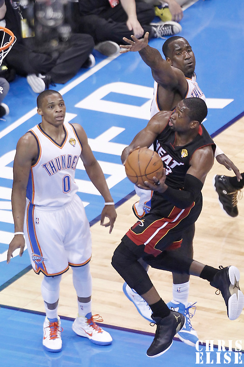 14 June 2012: Miami Heat shooting guard Dwyane Wade (3) goes to the basket past Oklahoma City Thunder center Kendrick Perkins (5) during the Miami Heat 100-96 victory over the Oklahoma City Thunder, in Game 2 of the 2012 NBA Finals, at the Chesapeake Energy Arena, Oklahoma City, Oklahoma, USA.