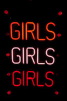 Girls written in neon lights against black background