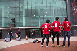 © Licensed to London News Pictures . 27/01/2014 . Manchester , UK . Thai tourists L-R Suthon Apinuntavach (50) , Putthipong W (35) and Soradetch Phetsangsailkul (35) pose with their new shirts . Their in Manchester to watch the Cardiff game tomorrow . Fans with new MATA 8 shirts in front of Old Trafford Football Ground as it's announced that Spaniard Juan Mata ( Juan Manuel Mata García ) has signed for Manchester United  . Photo credit : Joel Goodman/LNP