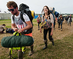 © Licensed to London News Pictures. 29/06/2015. Pilton, UK. Glastonbury Festival goers leave the site on the monday morning to queue for their buses home, and the cleanup operation to restore the site begins.  Photo credit: Richard Isaac/LNP