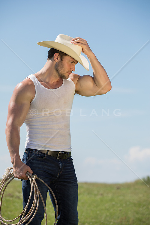 good looking cowboy in a tank top on a ranch