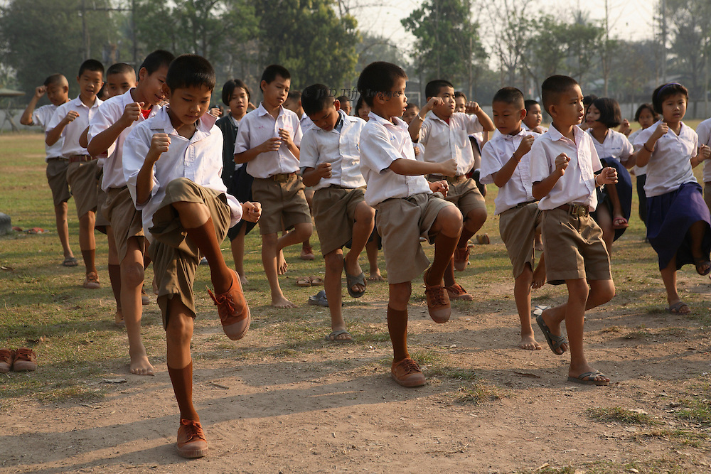 Class of middle school aged children performing a set of kickboxing preparation exercises.
