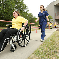 Haley Duke, 18, and a senior at Ingomar High School and a student in the Intro to Health Professions class through North East Mississippi Community College, pushes herself up a hill in a wheelchair to simulate the difficulty of getting around without assistance during Empathy Experience simulations at Longtown Medical Park Wednesday afternoon. Lauren Aday, an ICC student in the Occupational Therapy Assistant Program, guides Duke through the Empathy Experience where Duke gets a first hand idea of what its like to live with a disability and how Occupational Therapists help those to adapt.
