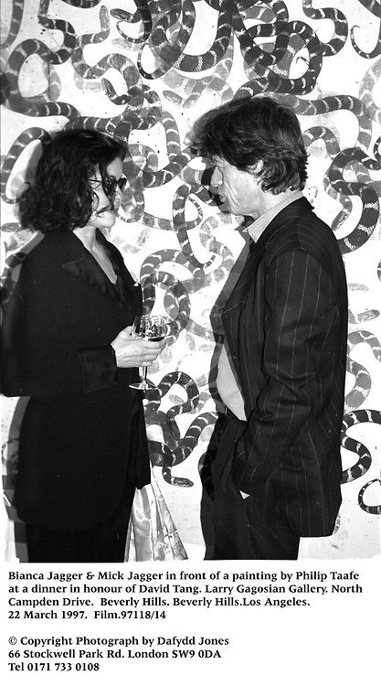 Bianca Jagger & Mick Jagger in front of a painting by Philip Taafe at a dinner in honour of David Tang. Larry Gagosian Gallery. North Cam[pden Drive. Beverly Hills. Beverly Hills.Los Angeles. 22 March 1997. Film.97118/14<br />