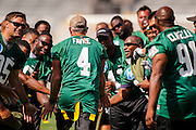 Former Green Bay Packers quarterback Brett Favre is greeted by fellow players before playing a chairity flag football game. Favre was inducted into the Packers Hall Fame the following day. (AP Photo/Andy Manis)