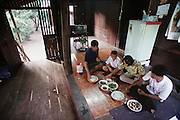 On a school morning, breakfast at the Khuenkaew's house, Bang Muang Wa village, outside Chiang Mai, Thailand. The Khuenkaew family lives in a wooden 728-square-foot house on stilts, surrounded by rice fields in the Ban Muang Wa village, outside the northern town of Chiang Mai, in Thailand. Material World Project.