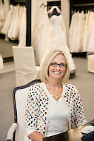 Portrait of a happy woman sitting on chair in bridal store