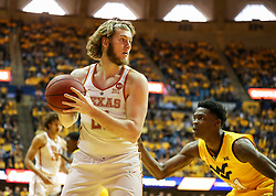 Jan 20, 2018; Morgantown, WV, USA; Texas Longhorns forward Dylan Osetkowski (21) holds the ball in the corner while defended by West Virginia Mountaineers forward Wesley Harris (21) during the first half at WVU Coliseum. Mandatory Credit: Ben Queen-USA TODAY Sports