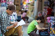 "12 APRIL 2012 - HO CHI MINH CITY, VIETNAM:   A vendor does his books in Binh Tay Market. Binh Tay market is the largest market in Ho Chi Minh City and is the central market of Cholon. Cholon is the Chinese-influenced section of Ho Chi Minh City (former Saigon). It is the largest ""Chinatown"" in Vietnam. Cholon consists of the western half of District 5 as well as several adjoining neighborhoods in District 6. The Vietnamese name Cholon literally means ""big"" (lon) ""market"" (cho). Incorporated in 1879 as a city 11 km from central Saigon. By the 1930s, it had expanded to the city limit of Saigon. On April 27, 1931, French colonial authorities merged the two cities to form Saigon-Cholon. In 1956, ""Cholon"" was dropped from the name and the city became known as Saigon. During the Vietnam War (called the American War by the Vietnamese), soldiers and deserters from the United States Army maintained a thriving black market in Cholon, trading in various American and especially U.S Army-issue items.       PHOTO BY JACK KURTZ"