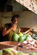 A man sells produce from an open-front store in Havana, Cuba.