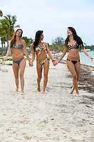 Three laughing sexy young women in bikinis walking hand in hand along the beach