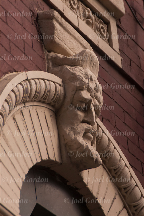Looking up at face in stone work on side of building  early 20th century,