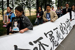 Protesting parents, whose children were killed in a school collapse during China's recent devastating earthquake, march, in Mianzhu, Sichuan province. The parents of the 127 children who died in the collapse kept marching Sunday and eventually met with higher officials, who told them the government would investigate.
