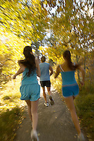 Joggers running through woodland rear view