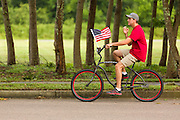 A bicyclist rides past with American flag during the Daniel Island ndependence Day parade July 3, 2015 in Charleston, South Carolina.