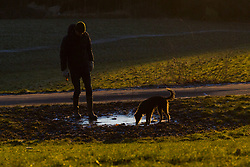 "A man and his dog examine a frozen puddle. The threatened snow from ""The Beast From The East"" weather system doesn't materialise overnight in London leaving a crisp, clear morning, seen from Hampstead Heath in North London. London, February 27 2018."