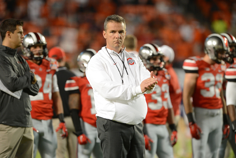 January 3, 2014: Head coach Urban Meyer of Ohio State watches his team warm up before the NCAA football game between the Clemson Tigers and the Ohio State Buckeyes at the 2014 Orange Bowl in Miami Gardens, Florida.