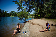Brooke Carter, left, and her niece, Emily Carter, 10 hang out at the American River in Sacramento, Calif. on July 1, 2011. Budget cuts have closed many of Sacramento's public pools. The American River is a popular alternative, but a deep Sierra snowpack has led to cold, swift flows and many rescues by emergency personnel.