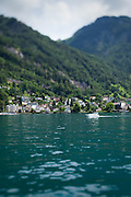 A lone motorboat in front of the town of Vitznau, Lake Lucerne, Switzerland.