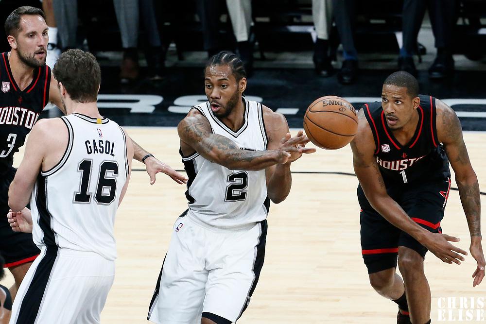 01 May 2017: San Antonio Spurs forward Kawhi Leonard (2) passes the ball past Houston Rockets forward Trevor Ariza (1) during the Houston Rockets 126-99 victory over the San Antonio Spurs, in game 1 of the Western Conference Semi Finals, at the AT&T Center, San Antonio, Texas, USA.