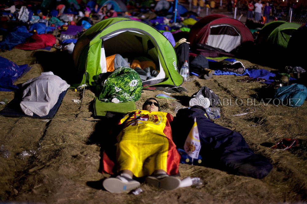 Pilgrims sleep over night waiting for Pope Pope Benedict XVI at the base of Cuatro Vientos, eight kilometres (five miles) southwest of Madrid on August 21, 2011.The pilgrims spent the night in the open air at the base of Cuatro Vientos, eight kilometres (five miles) southwest of Madrid, where Pope Benedict XVI celebrates the closing mass of the August 16-21 youth festival on Sunday morning