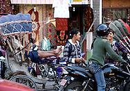 Local residents kick back after a ride through the city streets of Kathmandu.