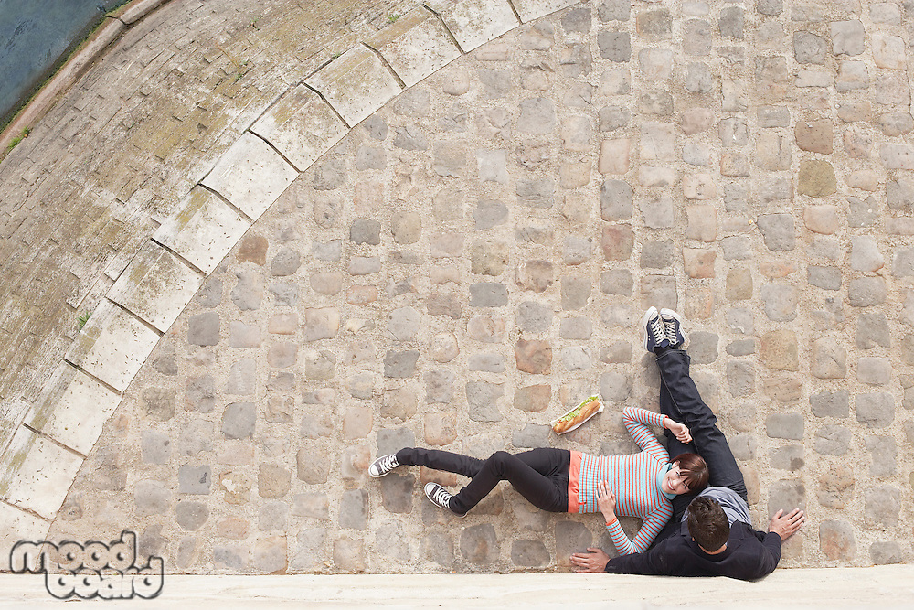 Couple Relaxing on cobble stones view from above