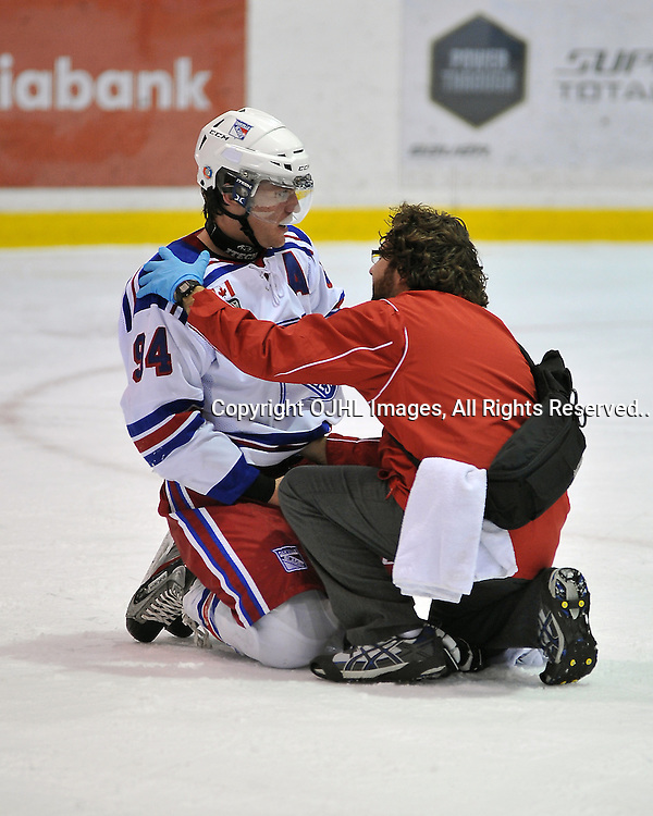 OAKVILLE, ON - Jan 25 : Ontario Junior Hockey League game between Hamilton Red Wings and Oakville Blades. Spencer Green #94 of the Oakville Blades is tended to by trainer JP Laciak during second period game action..(Photo by Shawn Muir / OJHL Images)