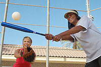 Senior woman hitting softball with other woman catching